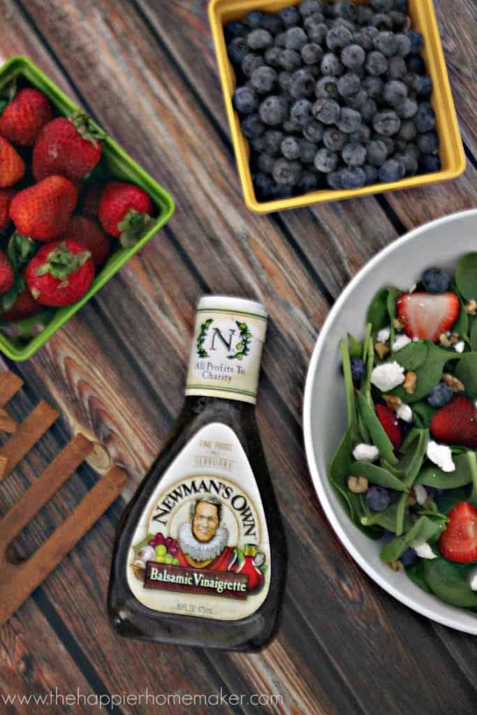 An above picture of a summer berry walnut balsamic salad next to strawberries, blueberries and Newman\'s Own salad dressing