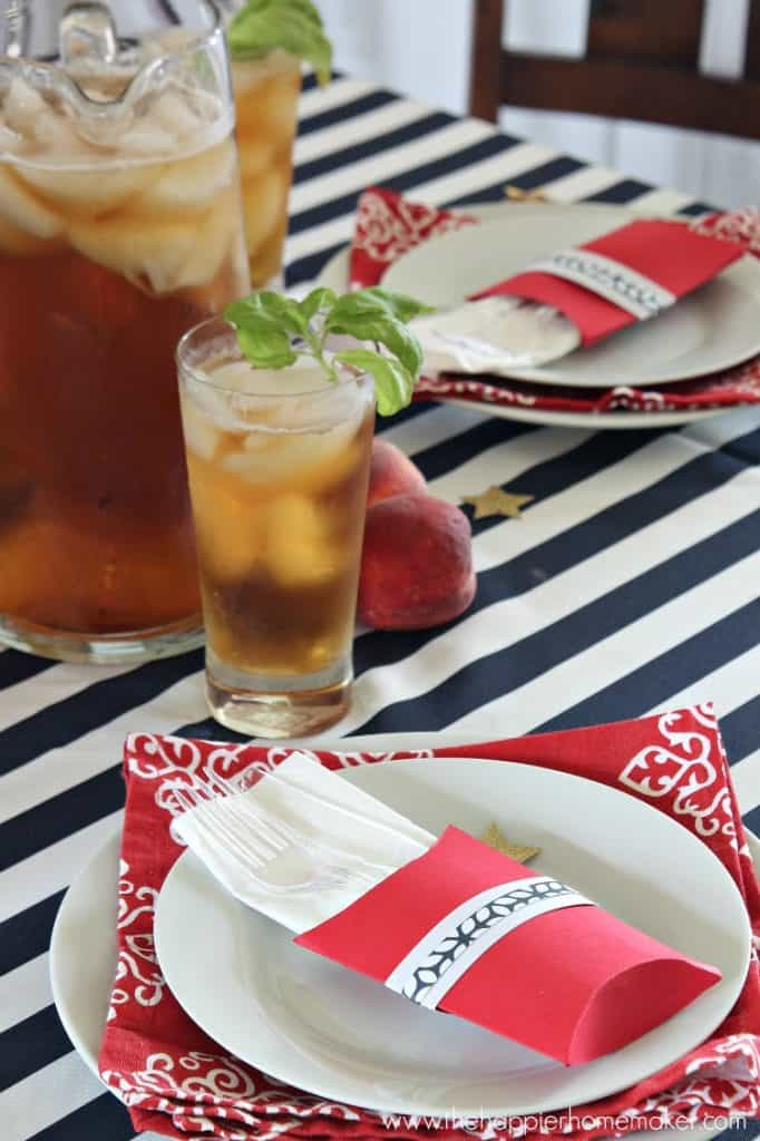 table with striped navy and white tablecloth and red and white place settings with iced tea pitcher and glass