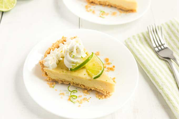 key lime pie with whipped cream and lime slice and zest