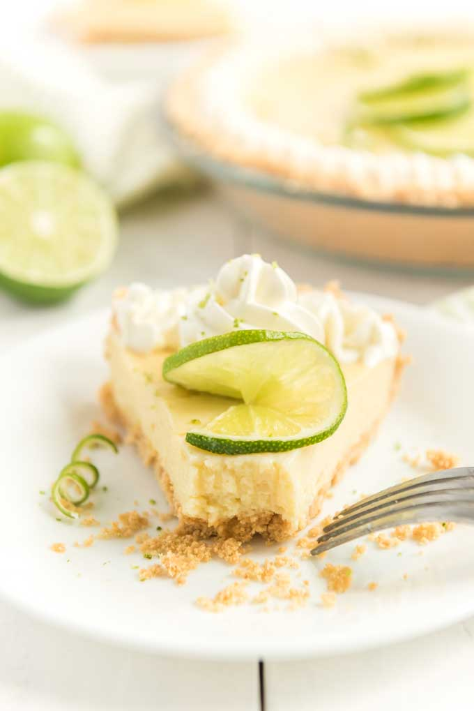 key lime pie slice with whipped cream and lime zest