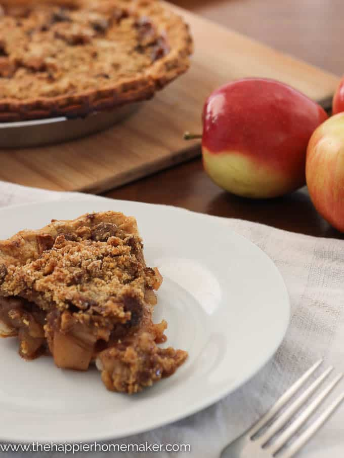 A slice of dutch apple crumble pie sitting on a white plate