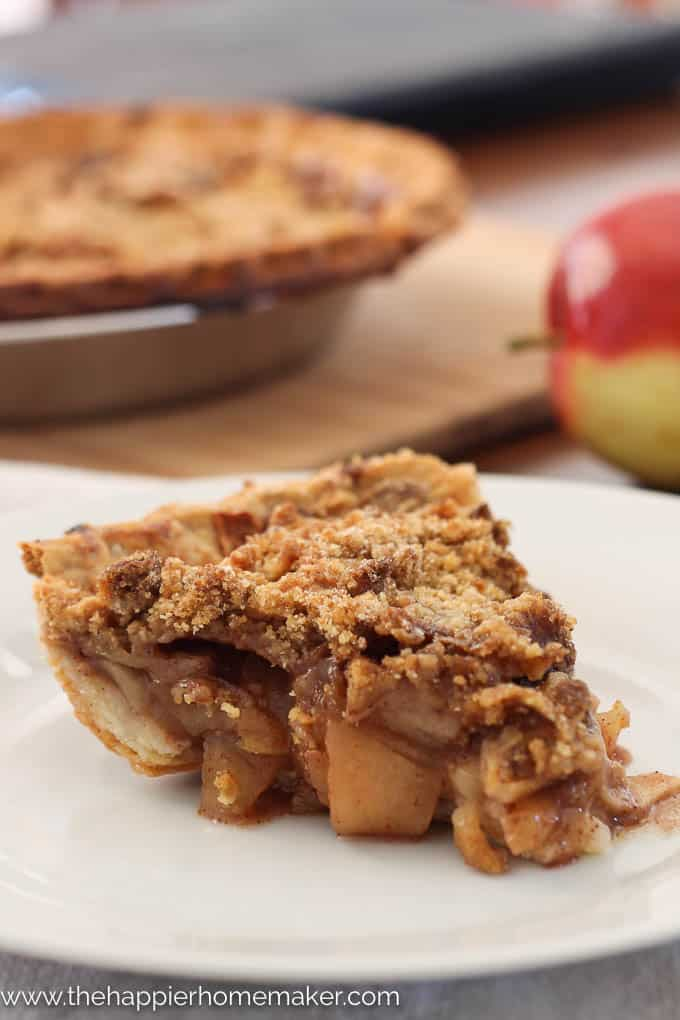 A close up of a slice of apple pie on a white plate with apple in background