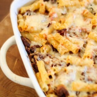 A close up of cheesy bacon baked ziti in a white baking dish