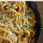pumpkin pasta sauce over thick noodles in cast iron skillet