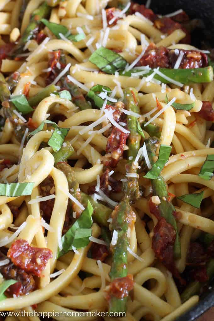 A close up of dried tomato asparagus pasta topped with cheese
