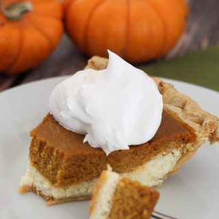 A partially eaten piece of layered cheesecake pumpkin pie topped with whipped cream