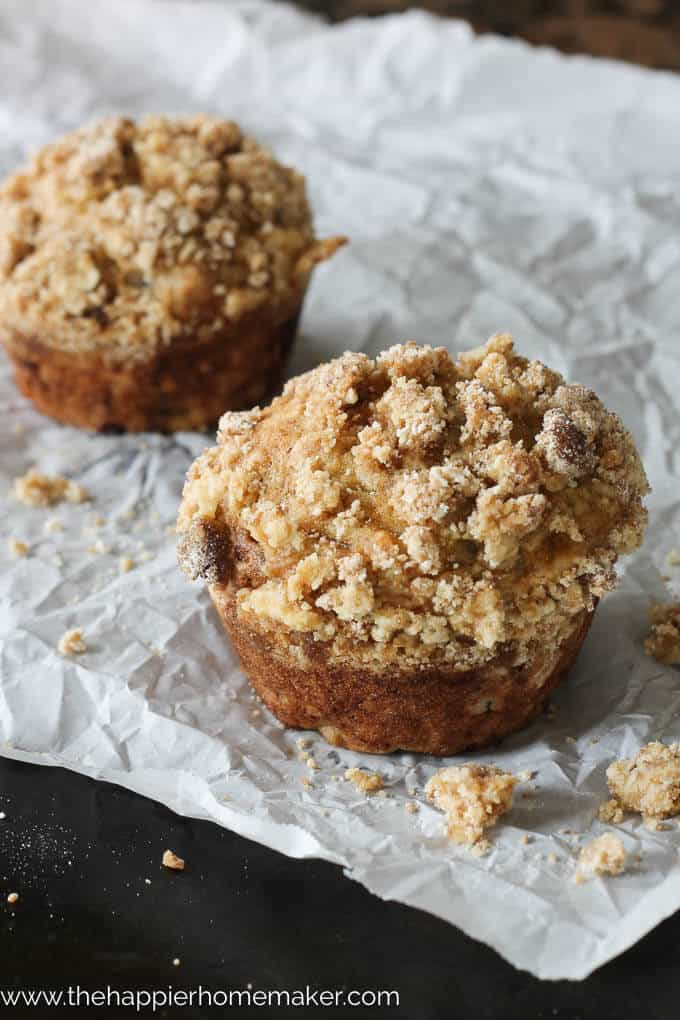A close up of two banana muffins with crumble toppings on wax paper