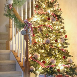 A brightly lit and decorated Christmas tree next to a stairwell