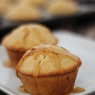 A close up of two honey cornbread muffins on a white serving dish