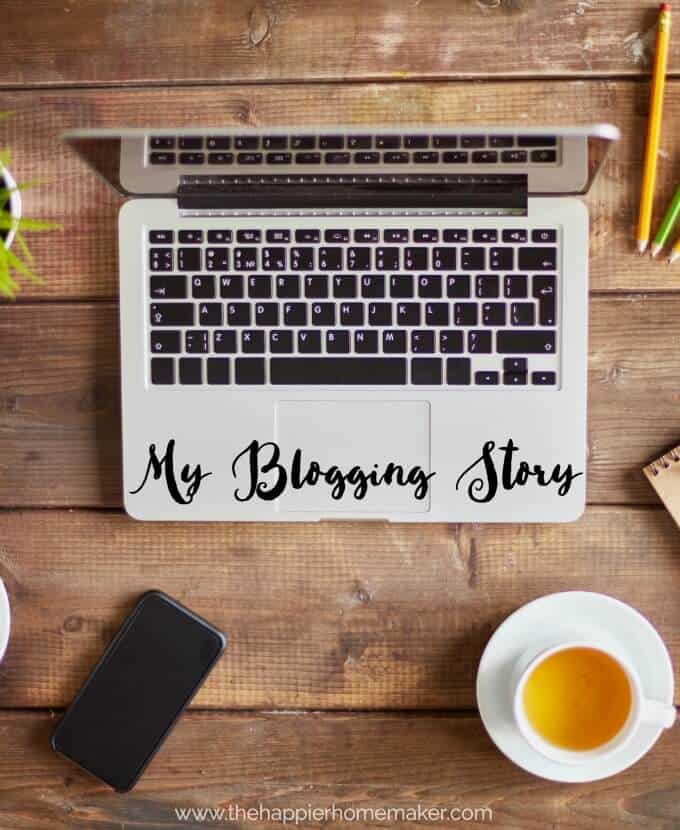 """An above picture of a laptop with the words \""""my blogging story\"""" written in cursive on the bottom of the computer with a cup of tea, pencils and paper nearby"""