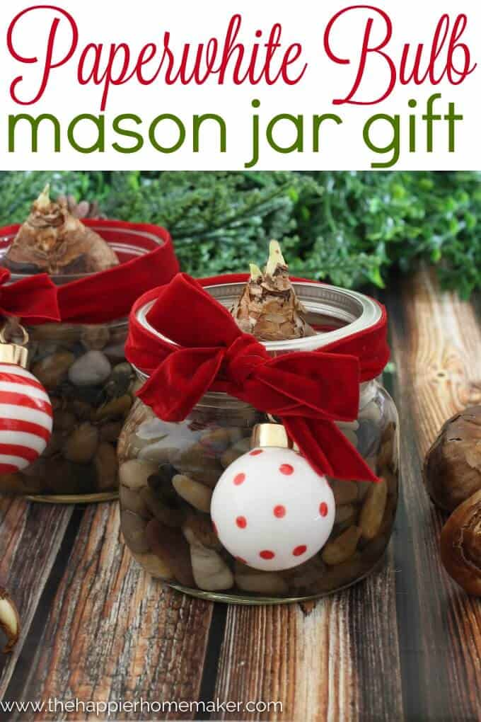A small mason jar filled with rocks as a paperweight with a velvet red ribbon and a white and red Christmas ornament