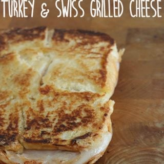 A close up of an inside out grilled Turkey Swiss sandwich on a wooden cutting board