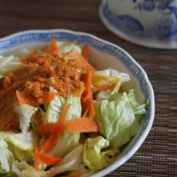 close up of salad in porcelain bowl with carrot ginger dressing on top
