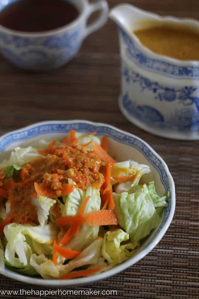 iceberg lettuce and shredded carrot in blue and white porcelain bowl with carrot ginger dressing on top