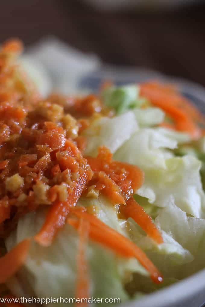 extreme close up of Japanese Ginger Salad Dressing over iceberg lettuce and shredded carrot