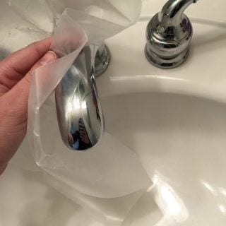 Someone rubbing plastic wrap on a chrome faucet to prevent water stains