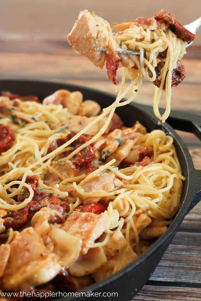 Cheesy pasta with chicken, bacon, and sun dried tomatoes in a cast iron skillet with fork