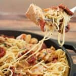 Tuscan chicken pasta on fork over pan