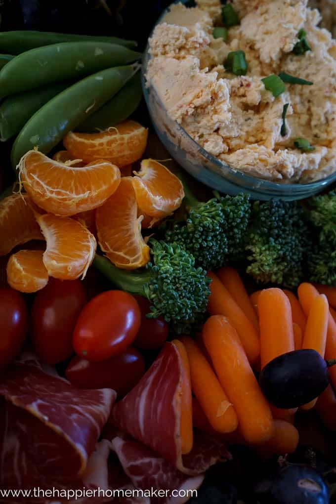 An assortment of peeled orange slices, carrots, grapes, crackers, dip, broccoli and prosciutto