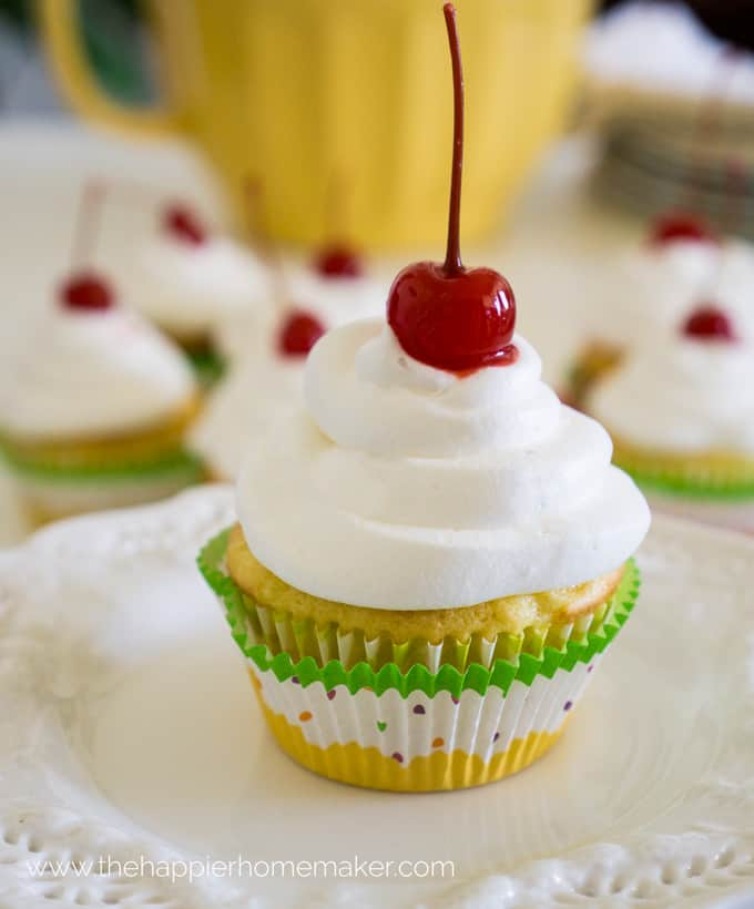 A close up of Maraschino Cherry Pineapple Cupcakes with a cherry on top