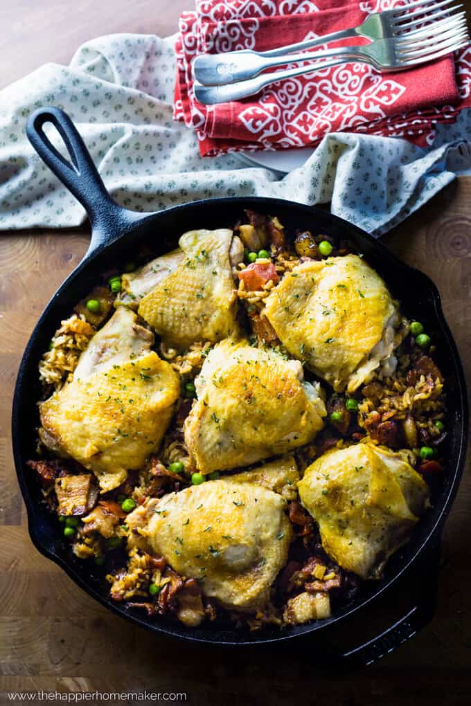 A cast iron pan full of Spanish rice chicken with kitchen towels in the background