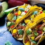 Three soft chicken tacos topped with avocados and peppers