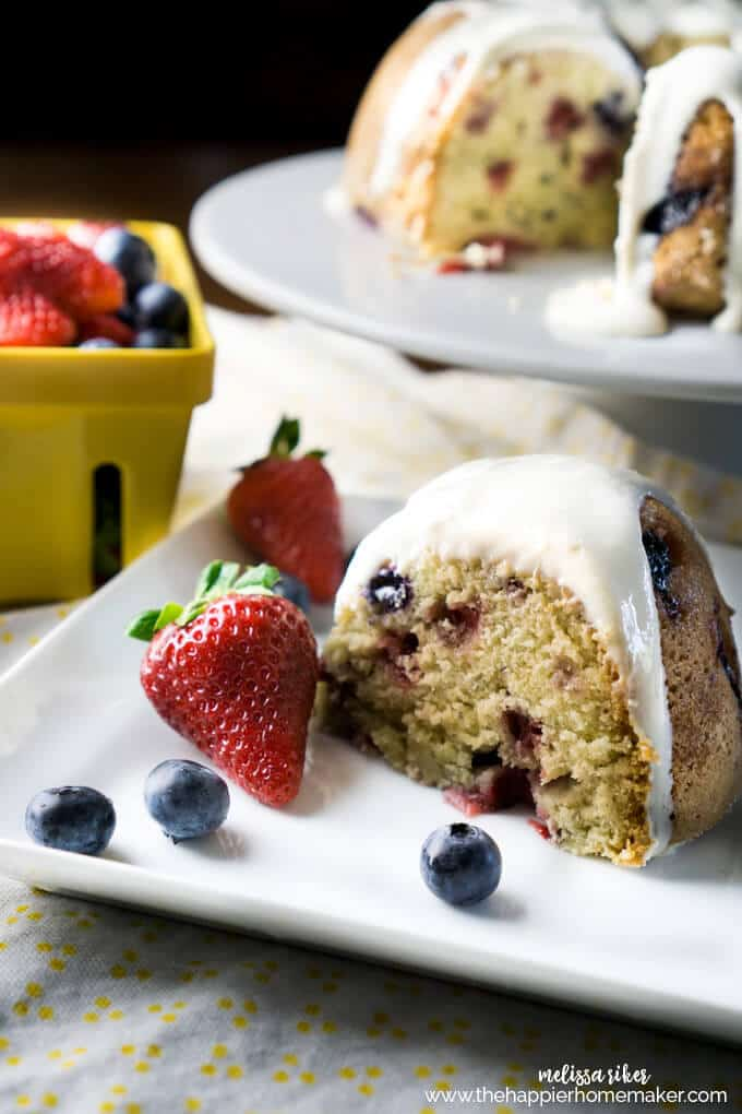 A piece of berry pound cake with a cream cheese glaze garnished with strawberries and blueberries