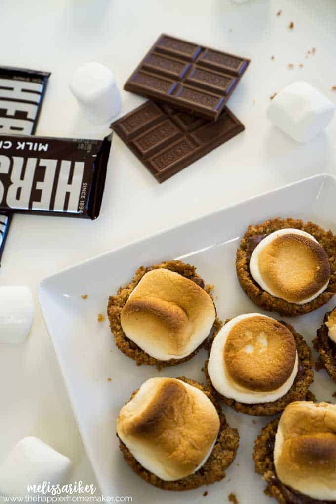 Delicious s'mores bites are all the fun of traditional s'mores with no campfire required! A buttery graham cracker crust topped with melted chocolate and roasted marshmallows. Amazing dessert for kids and adults!