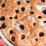 overhead view of blueberry cake in white dish with colorful napkin