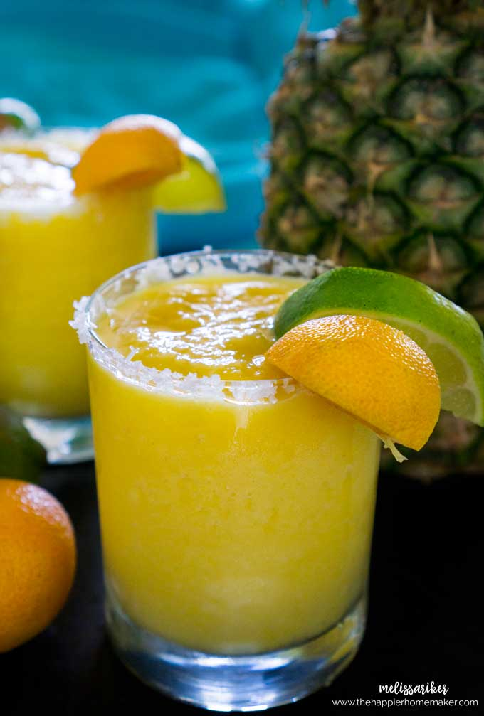 A close up of a frozen pineapple margarita garnished with a slice of lime and lemon in front of a pineapple