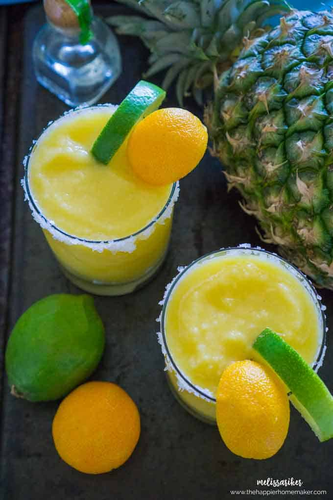 An above picture of two frozen pineapple margaritas garnished with a slice of lime and lemon in front of a pineapple