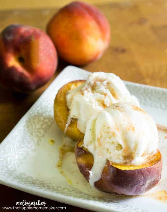 Baked peaches with brown sugar and cinnamon topped with ice cream on a small white platter