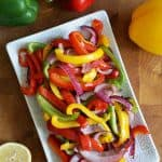 overhead view of roasted colorful bell pepper slices on white rectangle plate with whole peppers and lemon cut in half