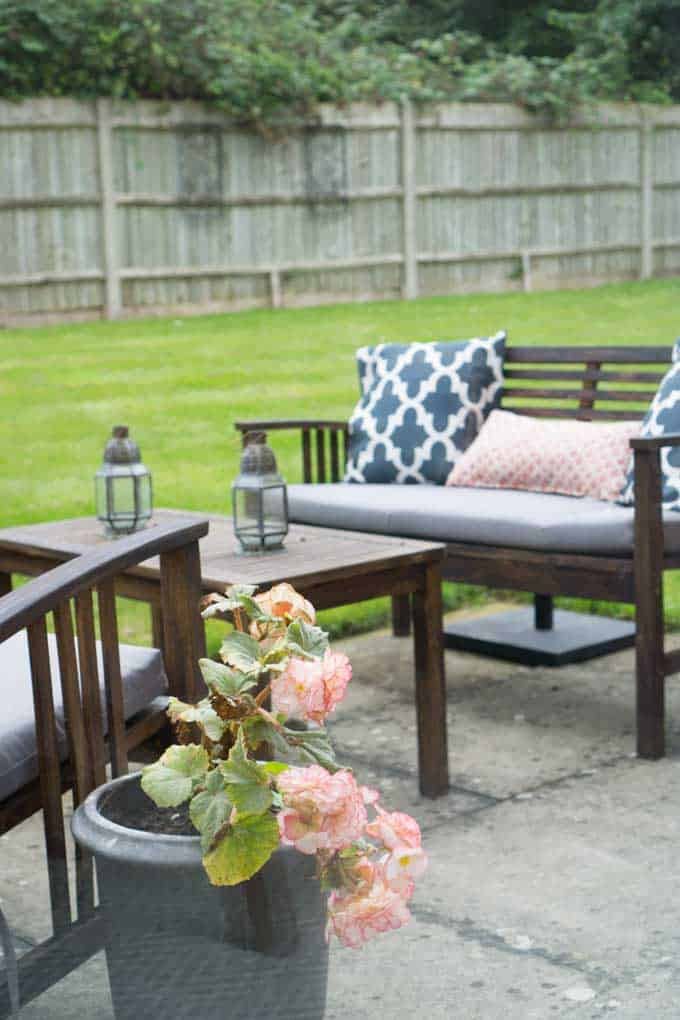 An outdoor furniture set with different pillows and candle holders