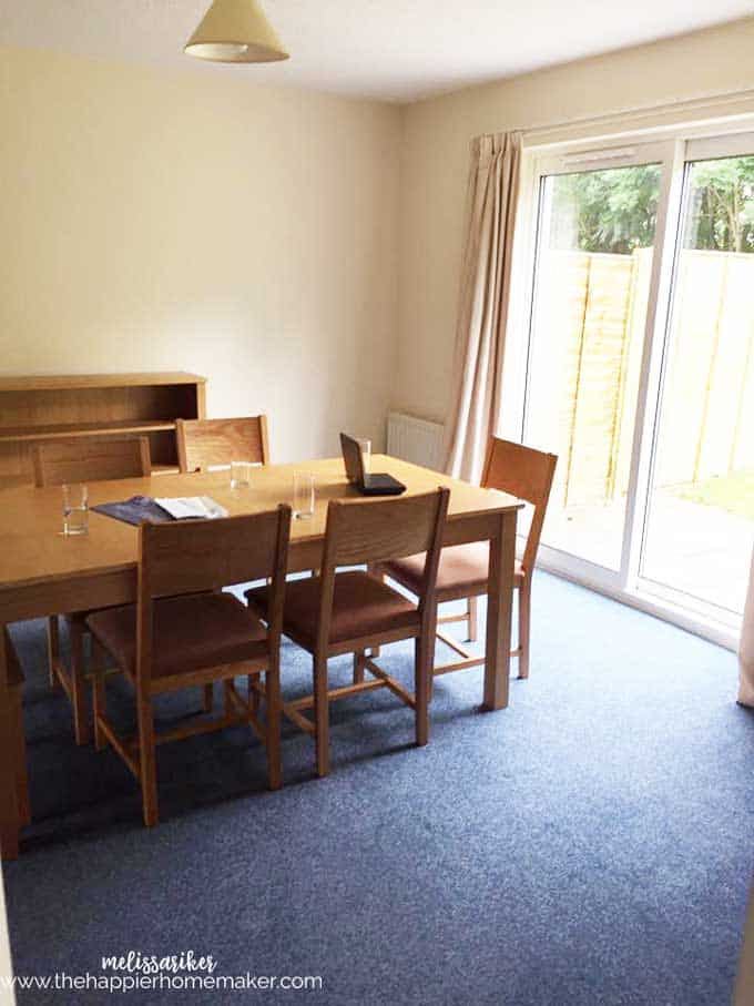 A plain dining room with a table and shelf in the background