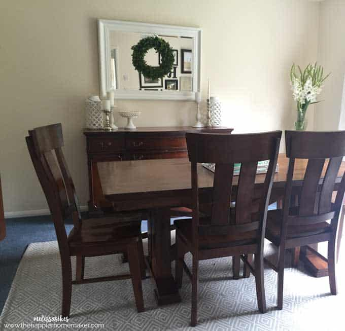 A brown dining room table with mirror and wreath in the background