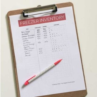 "A piece of paper titled ""Freezer Inventory"" on a clip board with a pen"