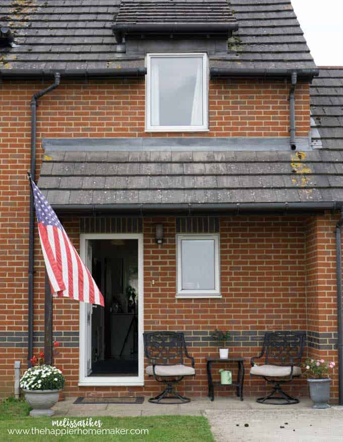 An American flag flying outside of a red brick home located in England