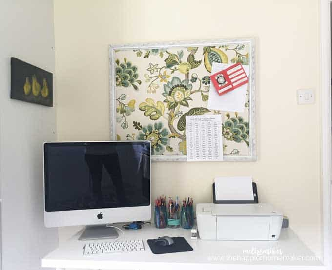 A desktop computer sitting on top of a desk with a printer next to it and a decorative pin board on the wall