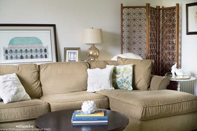 A green sofa with a lamp, coffee table and art