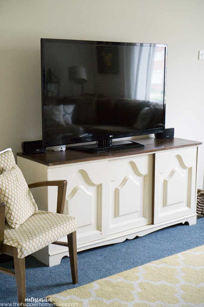 A tv sitting on a white bureau next to a chair