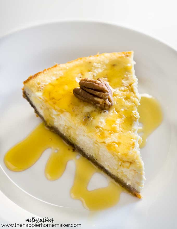 A slice of maple vanilla cheesecake on a white plate with syrup and pecan