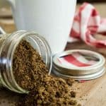 brown sugar coffee scrub pouring out of small mason jar laying on its side with white coffee cup and red gingham fabric in background