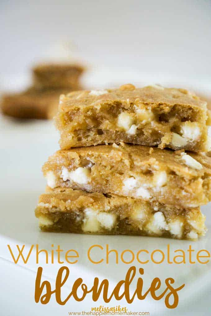 Three white chocolate blondies stacked on top of each other on parchment paper
