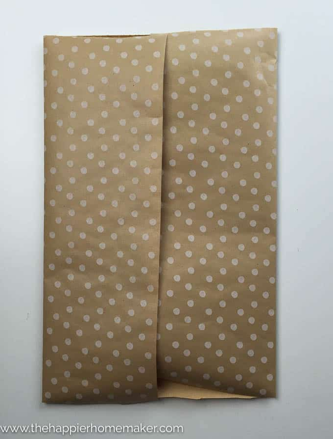 Brown and white wrapping paper folded to be used as a DIY gift bag