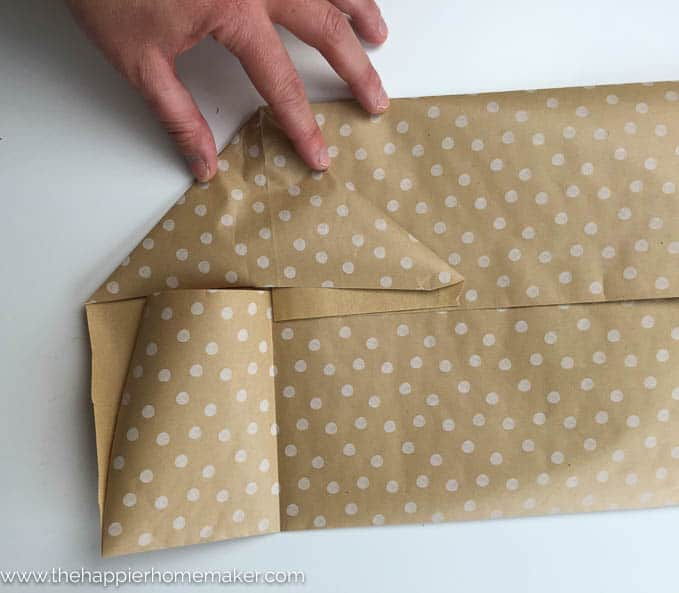 It's easy to make your own DIY Gift Bags in under 5 minutes using wrapping paper, tape and ribbon! Perfect for Christmas or wrapping oddly shaped presents!