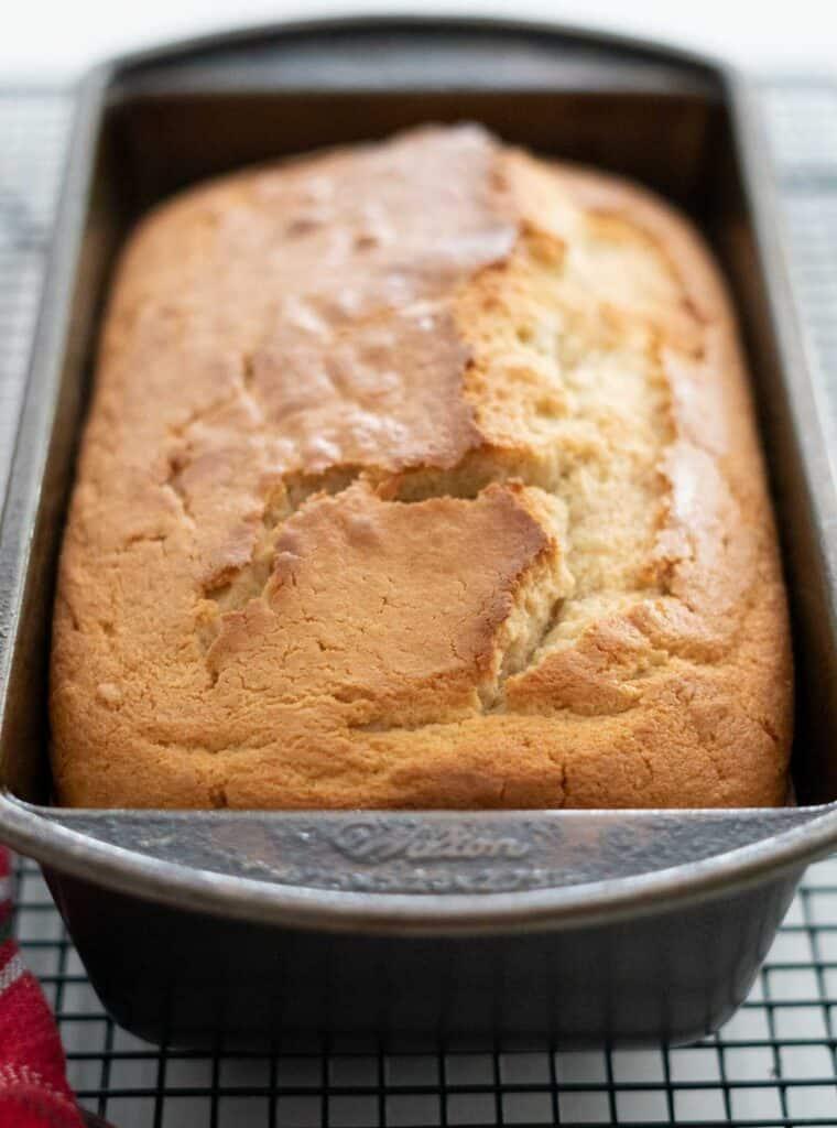 loaf of eggnog bread in pan on cooling rack