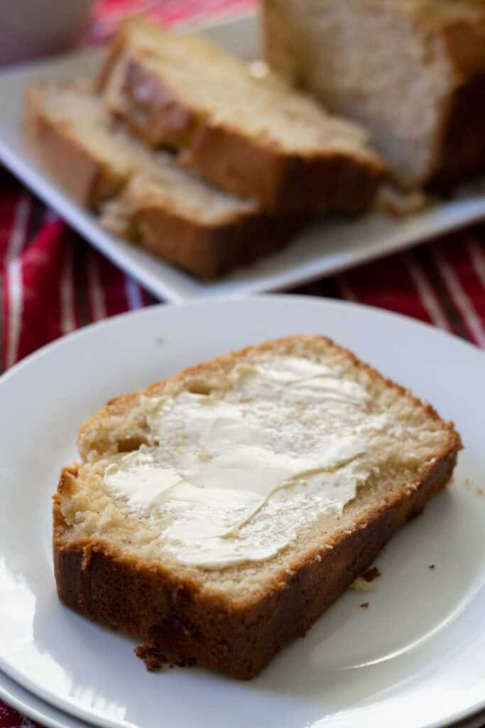 slice of bread with butter on it on white plate