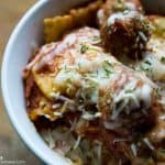 A bowl of slow cooker ravioli with meatballs topped with melted cheese