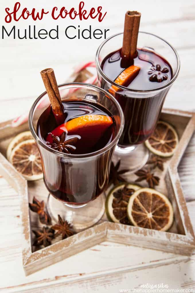 Two glasses of slow cooker Mulled Cider garnished with a slice of orange and cinnamon stick sitting on a wooden star tray